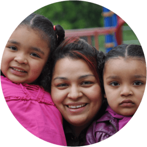 hispanic mom and two young daughters smiling